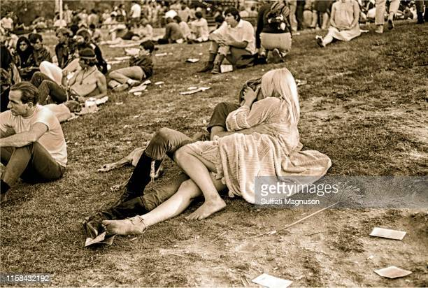 Kissing couple on bare grass who only have eyes for each other as surrounding crowd pays them no attention at the 1st Elysian Park Love-In on March...