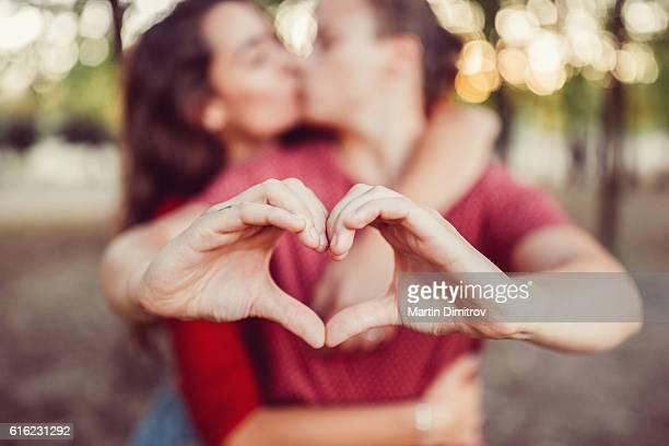Kissing couple showing heart shape symbol