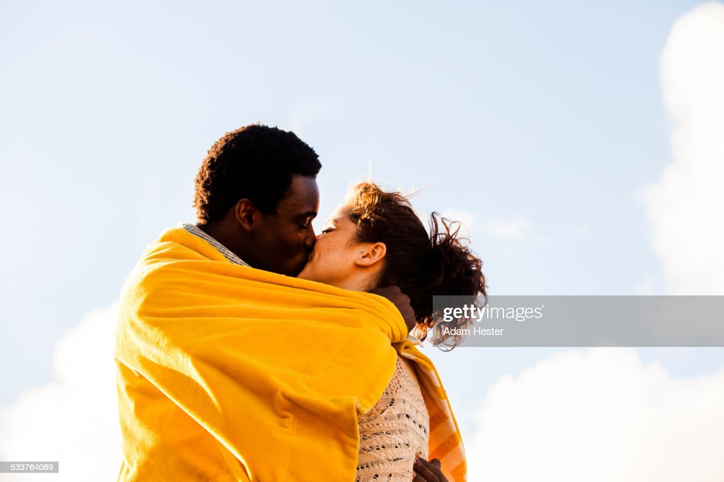 Kissing couple wrapped in blanket outdoors : Foto stock