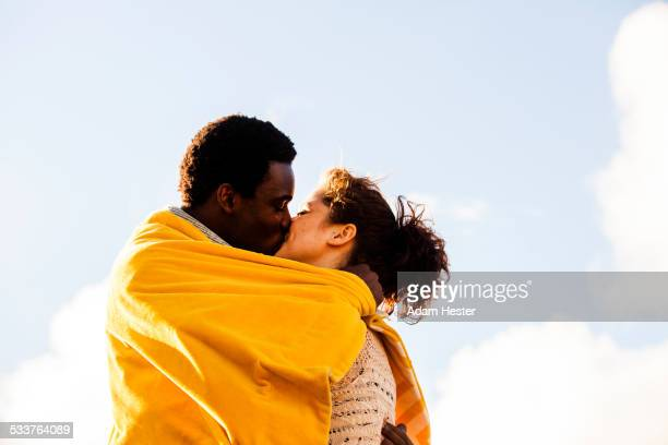 kissing couple wrapped in blanket outdoors - black women kissing white men stock pictures, royalty-free photos & images