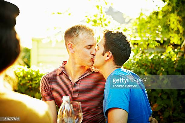 Kissing gay couple at backyard party with friends