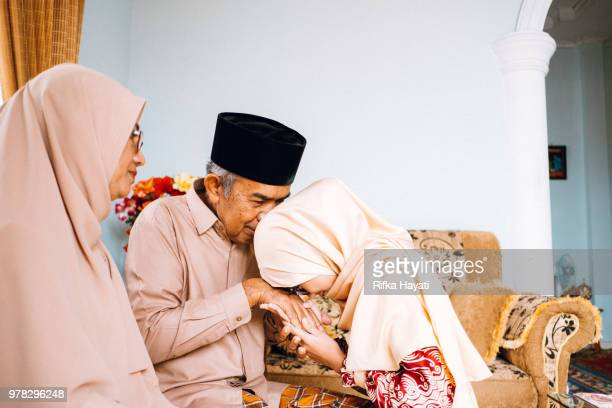 kissing hands of family members on eid - hari raya celebration stock pictures, royalty-free photos & images