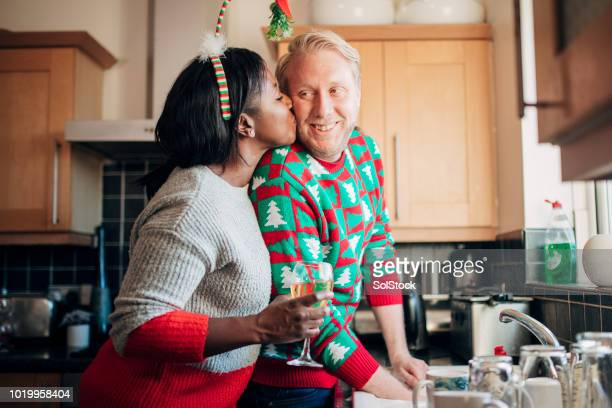 Kissing her Husband as he Washes the Dishes at Christmas