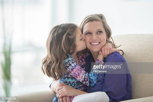 kissing her mom on the cheek - purple shirt stock photos and pictures