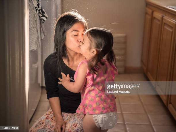 kissing her toddler girl in laundry room - diaper girl photos et images de collection