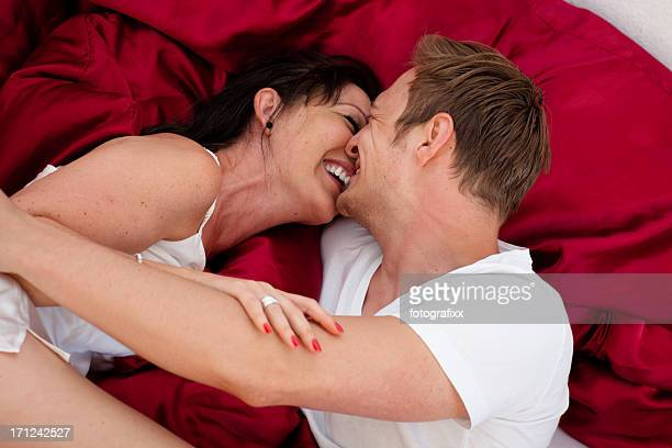 kissing heterosexual young couple in rumpled bed at morning - image stockfoto's en -beelden