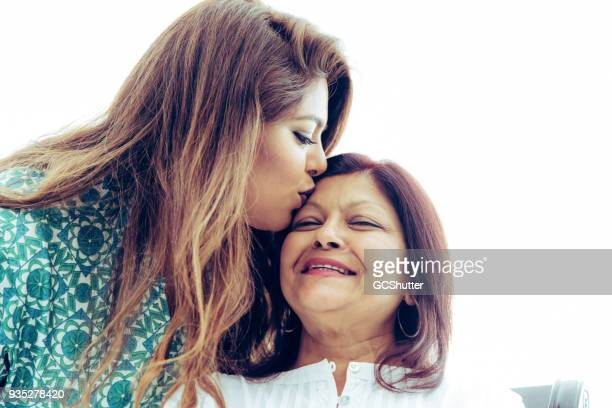 kissing the forehead of a loved one. - gulf countries stock pictures, royalty-free photos & images