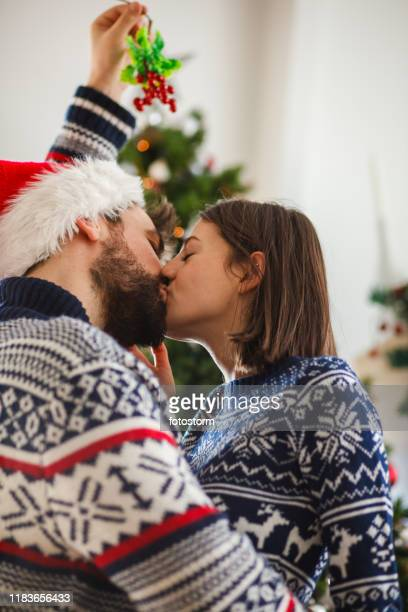 kissing under mistletoe - mistletoe stock photos and pictures