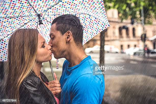 kissing under umbrella on a rainy day - couples kissing shower stock pictures, royalty-free photos & images