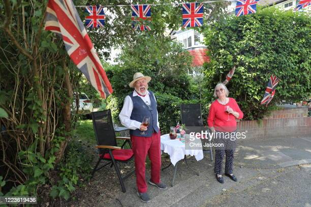 LONDON ENGLAND MAY 08 Kit and Gwen Peck celebrate VE Day outside their house in Sheen on May 08 2020 in London England The flag on the left and right...