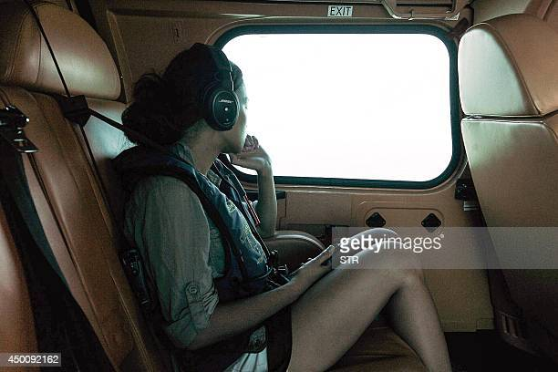 Kit Natariga Panyawatcharakun the girlfriend of missing British tourist Gareth Huntley looks out the window while on board a helicopter flying from...