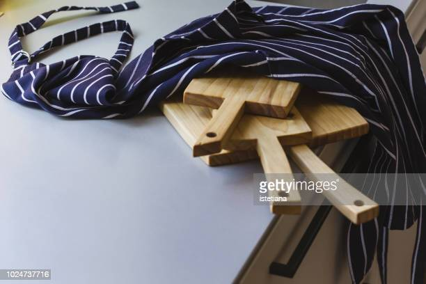 kitchen apron and wooden cutting boards on kitchen table - apron stock pictures, royalty-free photos & images