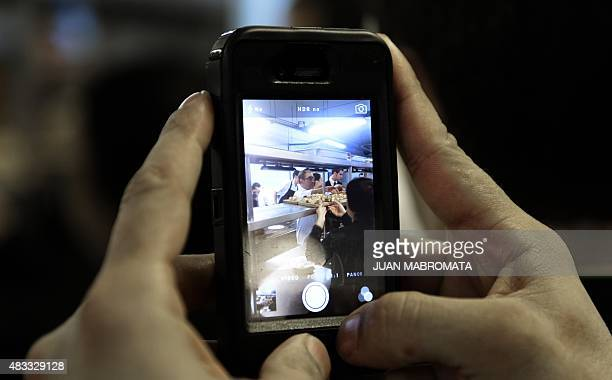 A kitchen assistant takes a snap of chef Jean Roca from the 'El Celler de Can Roca' at the kitchen of the Terrazas Bistro restaurant during a dinner...