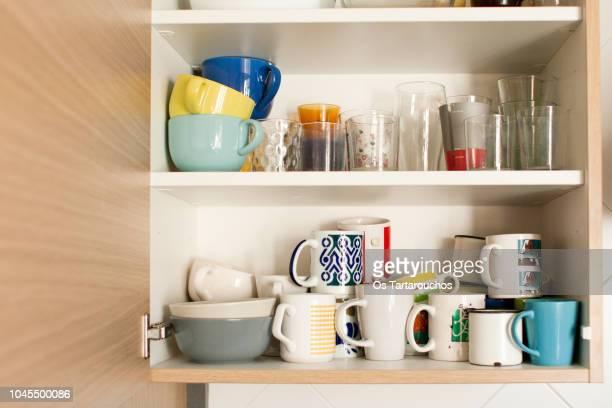 kitchen cabinet with mugs and glasses - armadietto da cucina foto e immagini stock