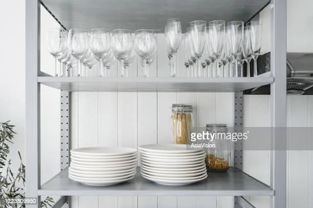 articoli da cucina, bicchieri da vino e piatti che espongono in un mobile da cucina domestico - articoli casalinghi foto e immagini stock