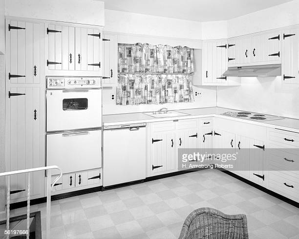 Kitchen Interior With White Wood Paneled Cabinets With Black Hinges And BuiltIn Appliances