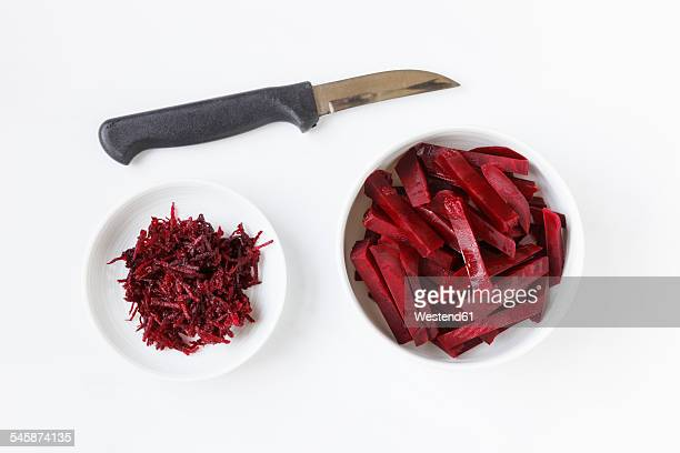 Kitchen knife and grated and sliced beetroot on white ground