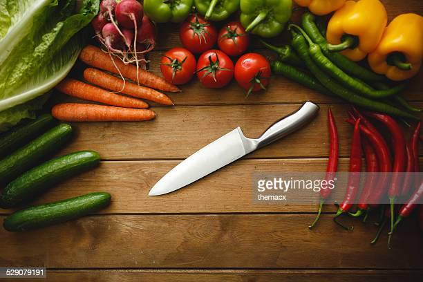 Kitchen knife and vegetables on wood