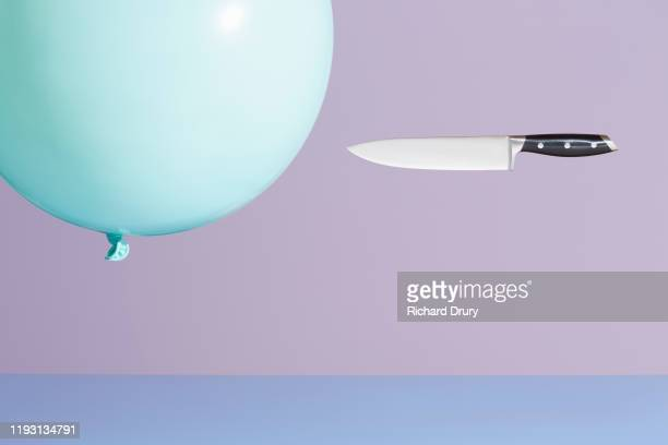 a kitchen knife chasing a  balloon - risk stock pictures, royalty-free photos & images