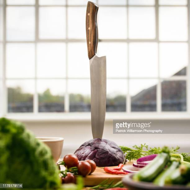 kitchen knife stuck in red cabbage on kitchen counter, still life - kitchen knife stock pictures, royalty-free photos & images