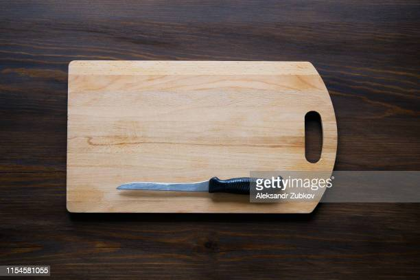 kitchen knife with black plastic handle on a wooden cutting board, close-up. copy space for text. the concept of kitchen utensils, cooking. - tablón fotografías e imágenes de stock
