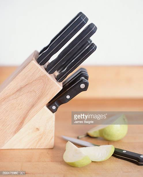 Kitchen knives and sliced pear