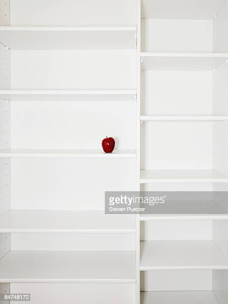 Kitchen pantry shelves displaying single apple
