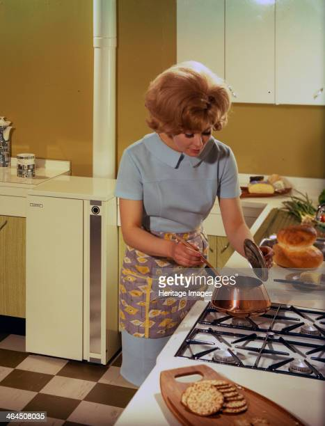 Kitchen scene Warwick Warwickshire 1966 A housewife attending to the cooking in her new kitchen The kitchen is the new fitted 'American' style with...