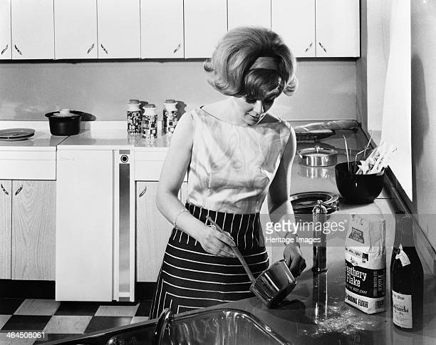 Kitchen scene Warwick Warwickshire 1966 A housewife cooking in her new kitchen The kitchen is the new fitted 'American' style with matching formica...