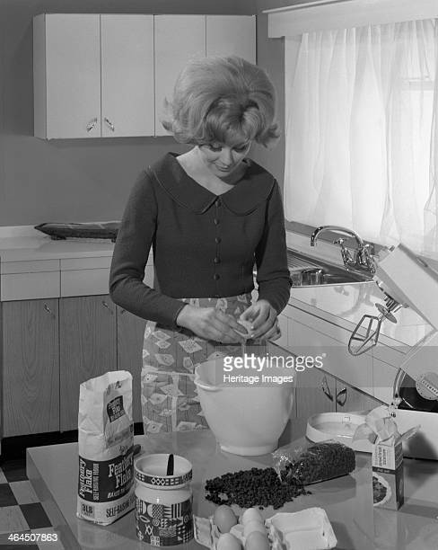 Kitchen scene Warwick Warwickshire 1966 In this advertising image a model is seen making a cake in her modern fitted kitchen with built in sink The...