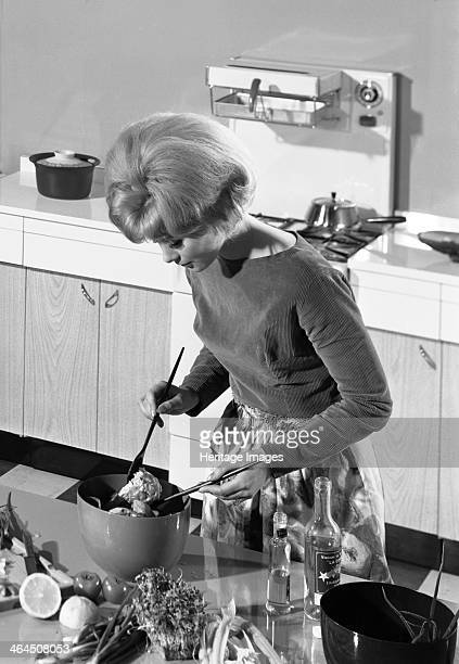Kitchen scene Warwick Warwickshire 1966 In this advertising image a model is seen preparing a salad in her modern fitted kitchen with a split level...