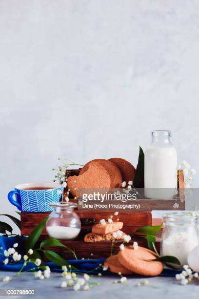 Kitchen shelf with baking ingredients for oatmeal cookies. Flour, milk and sugar on a light...