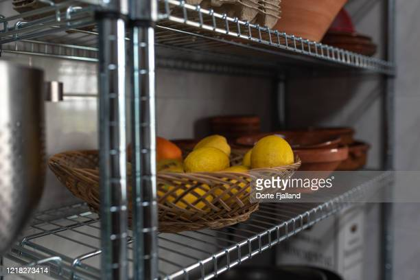 kitchen shelves with a basket of lemons and some earthenware crockery - dorte fjalland stock pictures, royalty-free photos & images