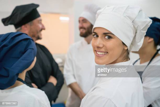 Kitchen staff at a meeting and sous chef looking at camera smiling