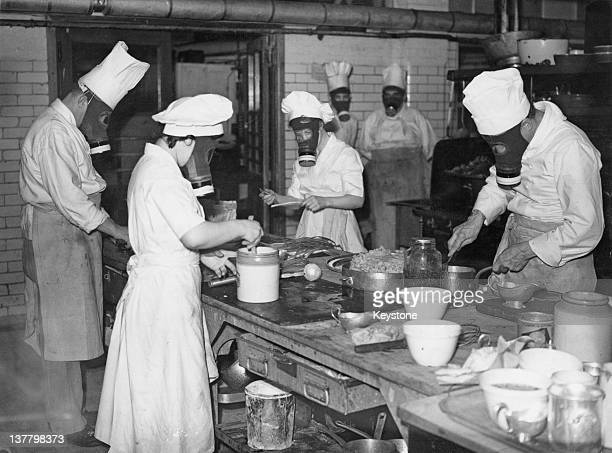 Kitchen staff at the Grosvenor House Hotel at work during a fifteenminute gas mask drill Mayfair London circa 1940