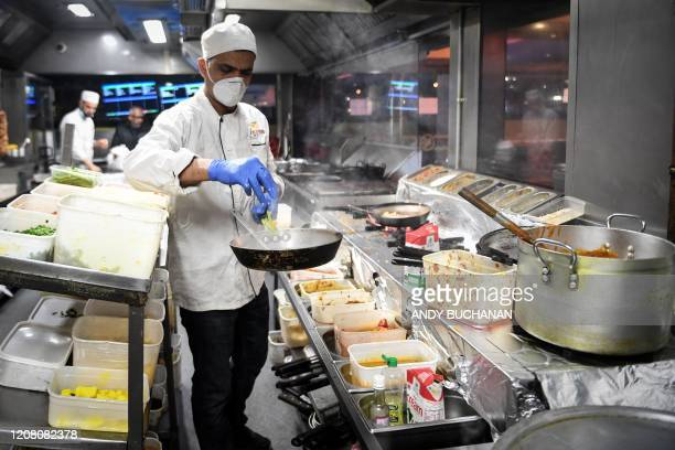 Kitchen staff at the Kebabish Grill restaurant in Glasgow wear masks as they prepare food on March 23, 2020 as the restaurant continues to operate as...