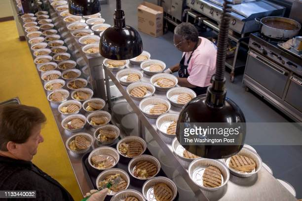 Kitchen staff at Trinity Cafe prepare meatloaf potatoes and steamed vegetables to be distributed by Feeding America on Wednesday morning March 27...