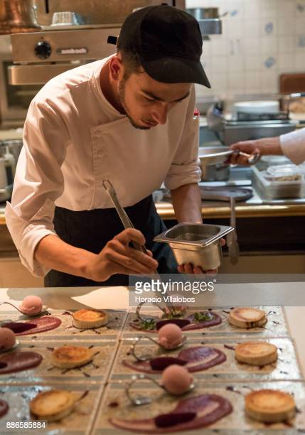 Kitchen staff prepare a dish of grated goat cheese with textures of pear Rocha during dinner cooking in Dolce CampoReal Lisboa Hotel for participants...