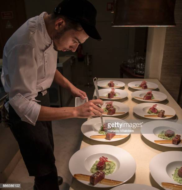 Kitchen staff prepare a dish of Tataki Tuna with sesame and seaweed grub rice during dinner cooking in Dolce CampoReal Lisboa Hotel for participants...