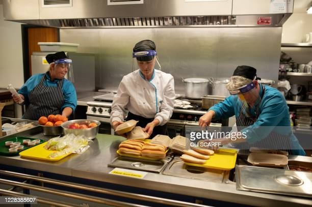 Kitchen staff prepare school lunches for pupils, which will be delivered to and eaten at their class desks, in order to reduce the movement of pupils...