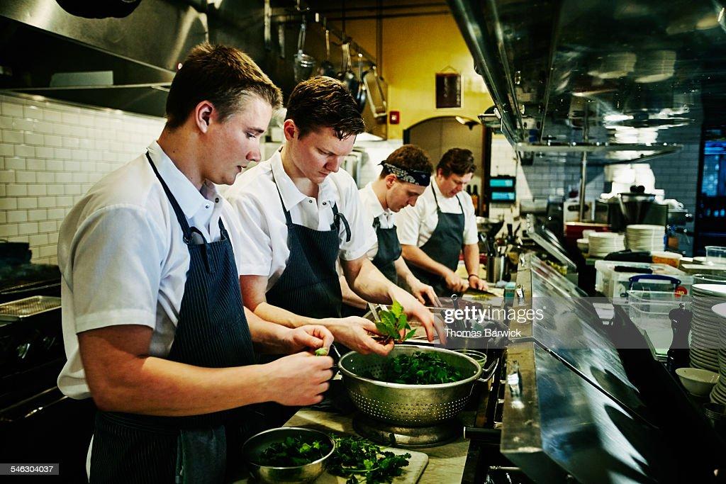 Kitchen staff preparing organic greens for dinner : Stock Photo