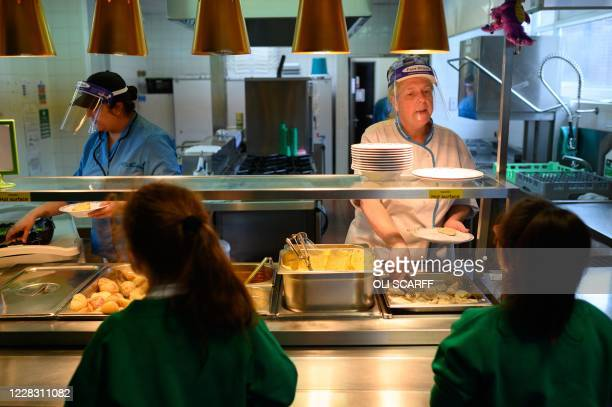 Kitchen staff wearing PPE face shields serve lunch at Greenacres Primary Academy in Oldham, northern England on September 02, 2020. - Millions of...