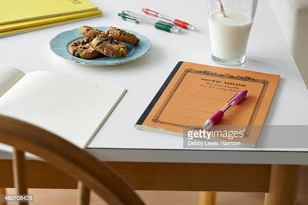 Kitchen table still life with notebooks, biscuits and milk