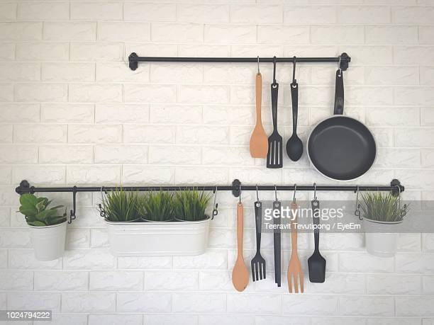 kitchen utensils and potted plants hanging against wall - cooking utensil stock photos and pictures