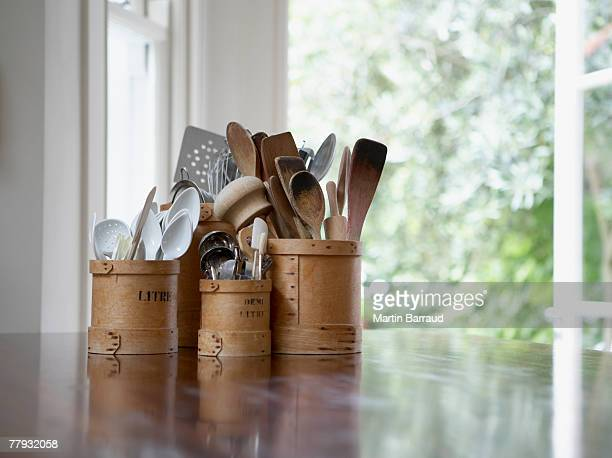 kitchen utensils in containers on table - cooking utensil stock photos and pictures