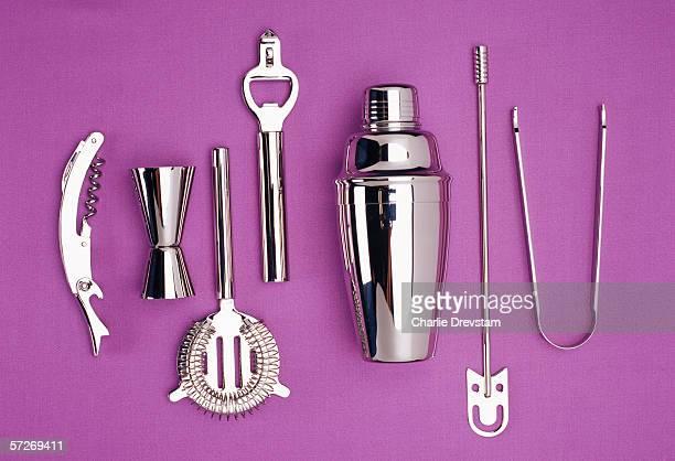 Kitchen utensils in stainless steel on a purple background.