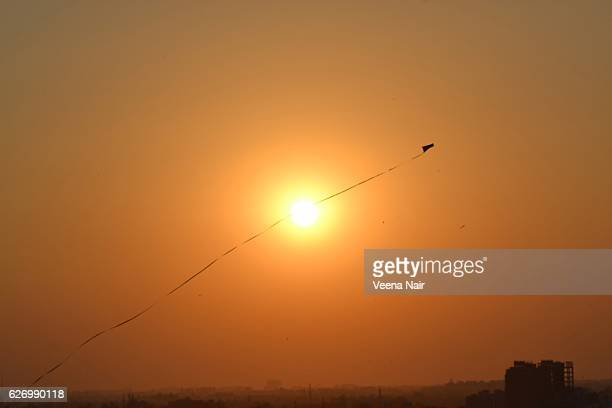 kite flying over the setting sun-ahmedabd-uttarayan-makar sankranti - makar sankranti stock pictures, royalty-free photos & images