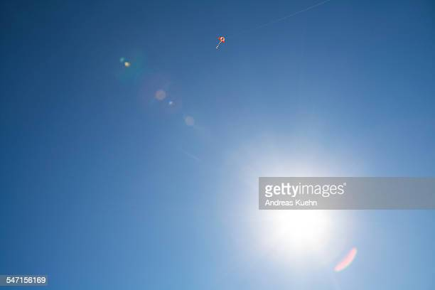 A kite in the blue sky with lens flare