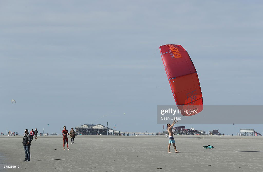 A kite surfer gets help hauling in his kite at a beach on July 18, 2016 at Sankt-Peter-Ording, Germany. Sankt-Peter-Ording is among the top destinations for vacationers along Germany's North Sea coast. Many Germans, unsettled by the recent terror attacks in countries like France and Turkey, are choosing to vacation in Germany this summer.