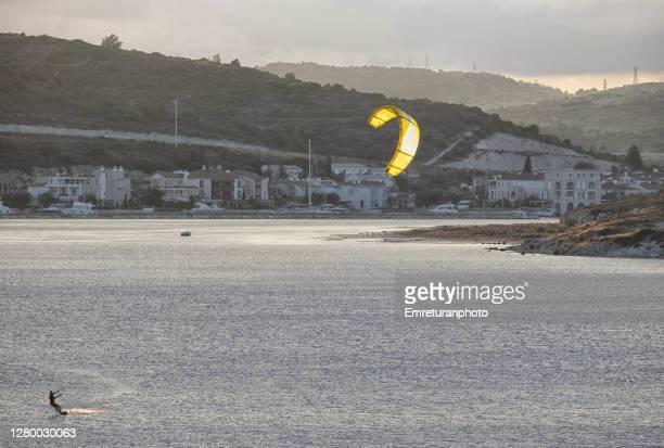 kite surfer in alacati bay on a cloudy autumn day - emreturanphoto fotografías e imágenes de stock
